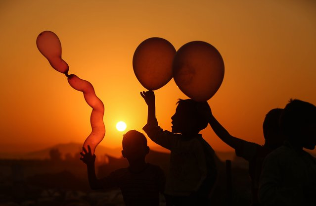 Syrian children play with balloons in the rebel-held town of Douma, on the eastern outskirts of Damascus, as Muslims celebrate the third day of the Eid al-Adha holiday on September 3, 2017. (Photo by Amer Almohibany/AFP Photo)