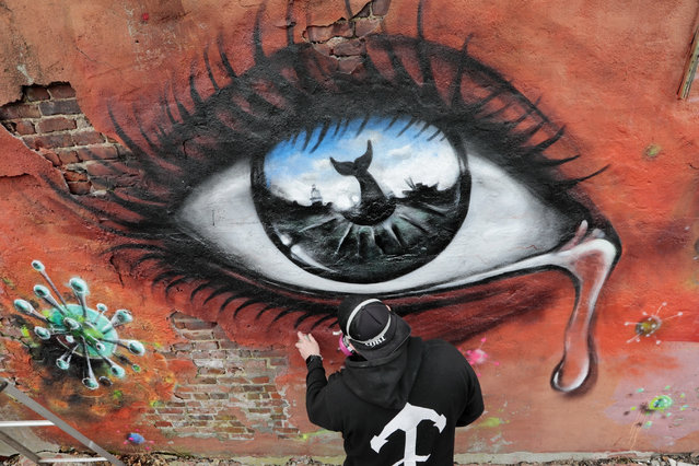 A graffiti artist works on a mural featuring a crying eye surrounded by coronavirus spores on a building adjacent to the Custom House Square in New Bedford, Connecticut on March 30, 2020. (Photo by Peter Pereira/AP Photo)