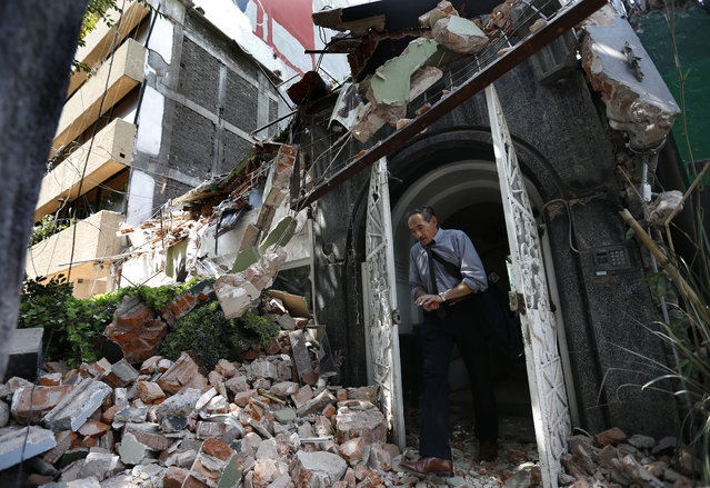 A man walks out of the door frame of a building that collapsed after an earthquake, in the Condesa neighborhood of Mexico City, Tuesday, September 19, 2017. (Photo by Marco Ugarte/AP Photo)