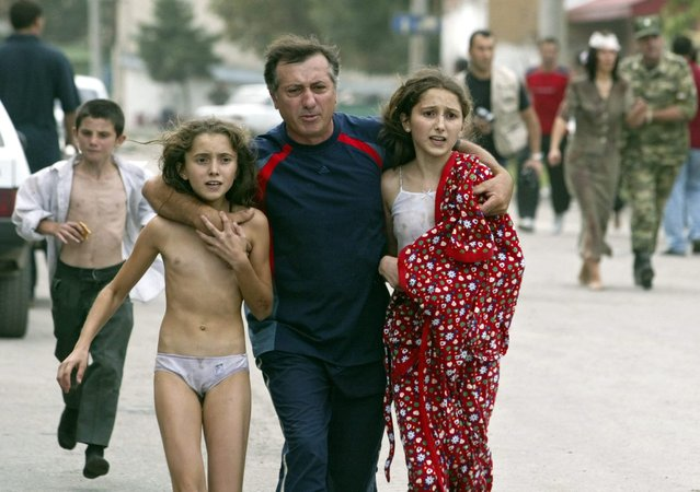 A man assists two young hostages who managed to escape from the school building after special forces entered the school in Beslan, North Ossetia, Friday 03 September 2004. Streams of hostages fled the besieged school in Beslan in southern Russia Friday amid intensive shooting and a series of powerful explosions that signalled a bloody end to the three-day stand-off with terrorists. (Photo by Yuri Kochetkov/EPA)