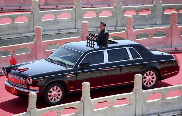 China's President Xi Jinping stands in a car as it drives past the Jinshui Bridge, at the beginning of the military parade to mark the 70th Anniversary of the end of World War Two, in Beijing, China, September 3, 2015. Xi announced on Thursday he would cut troop levels by 300,000 as China held its biggest display of military might in a parade to commemorate victory over Japan in World War Two, an event shunned by most Western leaders. (Photo by Reuters/China Daily)