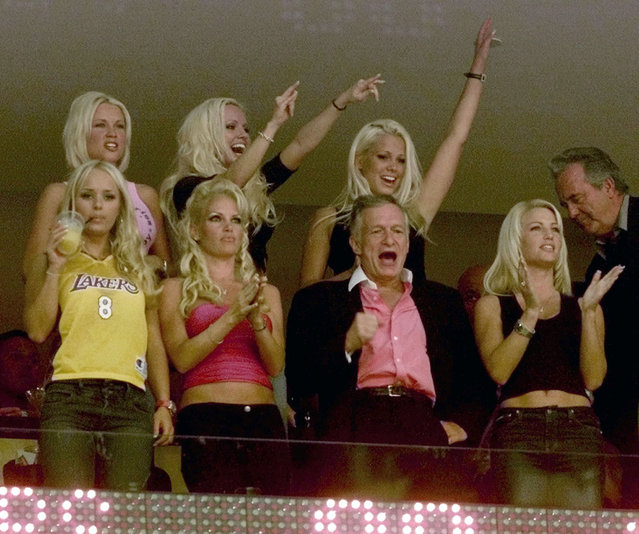 Hugh Hefner and several Playmates cheer during the NBA Finals between the Philadelphia 76ers and Los Angeles, June 2001. (Photo by Mike Blake/Reuters)