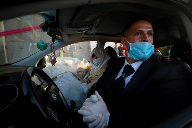 A Palestinian groom, Rafeh Qassim, wears a mask as he sits in a car with his bride on their wedding day amid concerns about the spread of the coronavirus disease (COVID-19), in Ramallah in the Israeli-occupied West Bank on April 18, 2020. (Photo by Mohamad Torokman/Reuters)