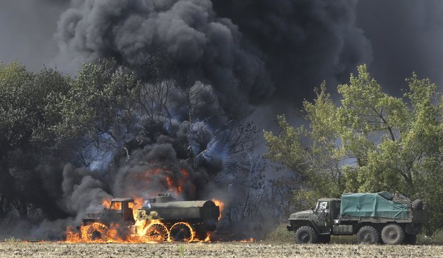 An unmarked military vehicle burns on a country road in the village of Berezove, eastern Ukraine, Thursday, September 4, 2014, after a clash between pro-government troops and Russian-backed separatist militia. Separatist rebels have made major strides in their offensive against Ukrainian government forces in recent days, drawing on what Ukraine and NATO says is ample support from the Russian military. (Photo by Sergei Grits/AP Photo)