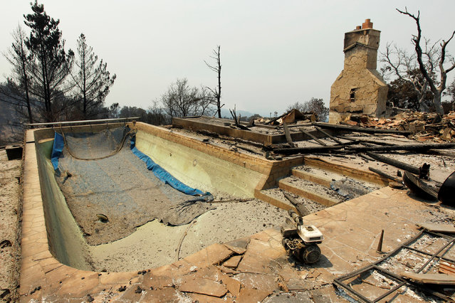 A swimming pool and a chimney remain at the site of a destroyed house after the Soberanes Fire burned through the Palo Colorado area, north of Big Sur, California, July 31, 2016. (Photo by Michael Fiala/Reuters)