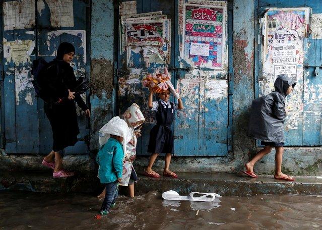 A woman accompanies schoolchildren through a flooded street during monsoon rains in Mumbai, India, August 1, 2016. (Photo by Danish Siddiqui/Reuters)