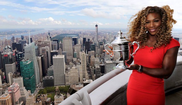 Serena Williams holds the U.S. Open tennis women's singles championship trophy during a visit to the 103rd floor of the Empire State Building, Monday, September 8, 2014, in New York. Williams defeated Caroline Wozniacki, 6-3, 6-3 on Sunday. (Photo by Charles Krupa/AP Photo)
