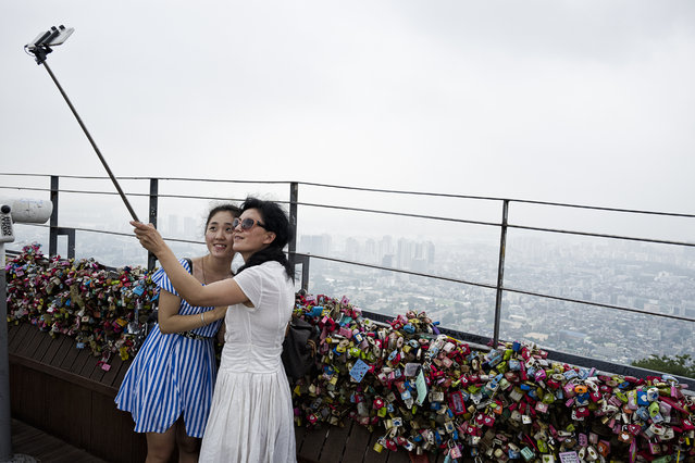Tourists take selfie with a selfie stick at the observation deck at N Seoul Tower on the top of Namsan mountain on July 29, 2015 in Seoul, South Korea. Thousands of key locks are locked fences as souvenirs or symbol of love by visitors. (Photo by Shin Woong-jae/The Washington Post)