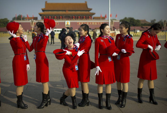 Hospitality staff members laugh as they stand on Tiananmen Square before the closing ceremony of China's 19th Party Congress at the Great Hall of the People in Beijing, Tuesday, October 24, 2017. The ruling Communist Party on Tuesday formally lifted Xi Jinping's status to China's most powerful ruler in decades, setting the stage for the authoritarian leader to tighten his grip over the country while pursuing an increasingly muscular foreign policy and military expansion. (Photo by Mark Schiefelbein/AP Photo)