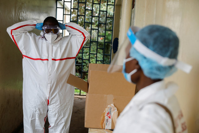 A health worker dresses in a protective suit before starting to perform the coronavirus testing in an effort to stop the spread of the coronavirus disease (COVID-19) in the Kibera slum of Nairobi, Kenya, May 26, 2020. (Photo by Baz Ratner/Reuters)