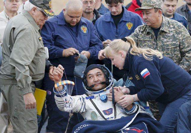 Kazakhstan's cosmonaut Aidyn Aimbetov holds a toy after landing near the town of Dzhezkazgan (Zhezkazgan), Kazakhstan, September 12, 2015. (Photo by Yuri Kochetkov/Reuters)