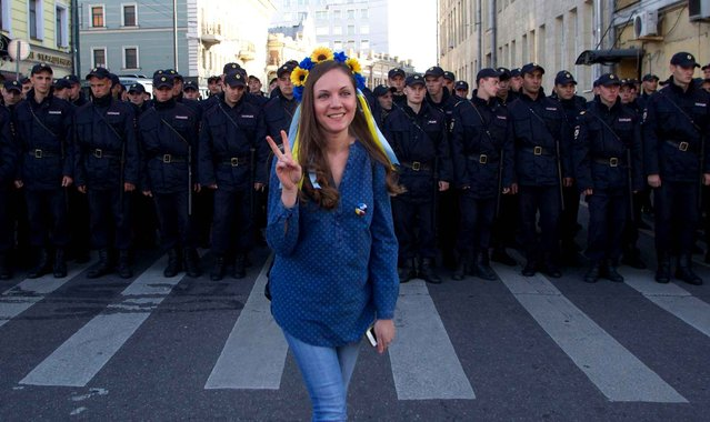 A woman wearing traditional Ukrainian flower headband poses for a photo in front of police officers, during an anti-war rally in downtown Moscow, Russia, Sunday, September 21, 2014. Thousands of people were marching through central Moscow to demonstrate against the fighting in Ukraine. (Photo by Denis Tyrin/AP Photo)