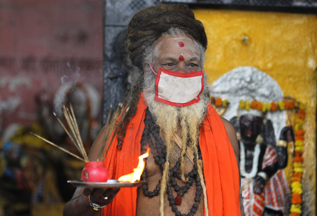 An Indian priest covers his face with a mask as a precaution against coronavirus and prays at a temple, in Prayagraj, India, Monday, June 8, 2020. (Photo by Rajesh Kumar Singh/AP Photo)
