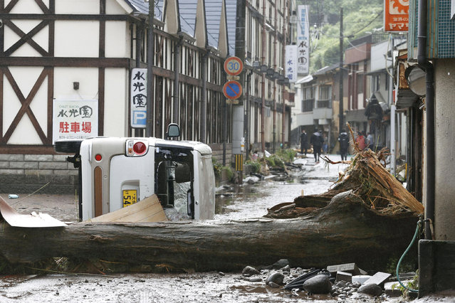 A vehicle and a tree lie down following a heavy rain in Hita, Oita prefecture, southern Japan Wednesday, July 8, 2020. Floodwaters flowed down streets in southern Japanese towns hit by heavy rains. (Photo by Kyodo News via AP Photo)