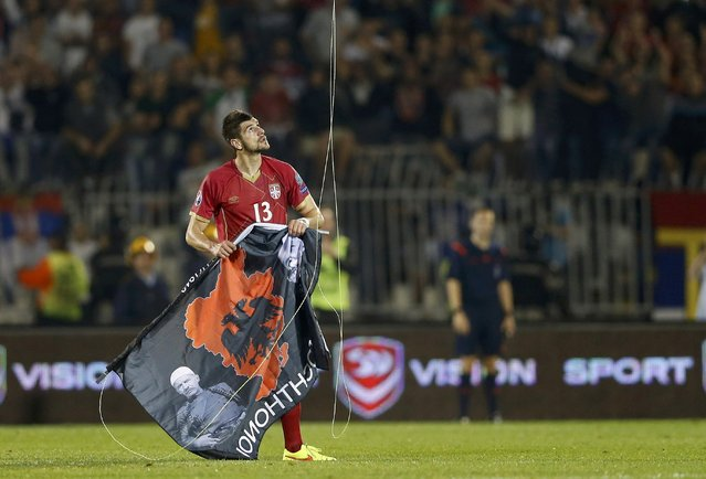 Stefan Mitrovic of Serbia grabs a flag depicting so-called Greater Albania, an area covering all parts of the Balkans where ethnic Albanians live, that was flown over the pitch during their Euro 2016 Group I qualifying soccer match against Albania at the FK Partizan stadium in Belgrade October 14, 2014. (Photo by Marko Djurica/Reuters)