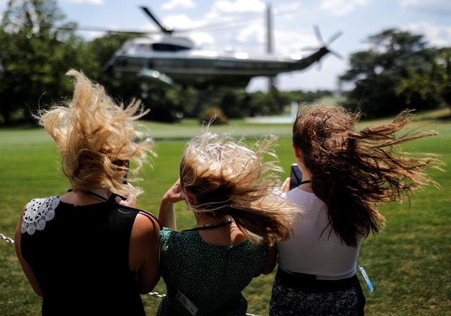Visitors withstand a strong gust of wind created by Marine One as they watch the helicopter ascend with U.S. President Donald Trump aboard as he departs for travel to Atlanta, Georgia from the South Lawn at the White House in Washington, U.S., July 15, 2020. (Photo by Carlos Barria/Reuters)