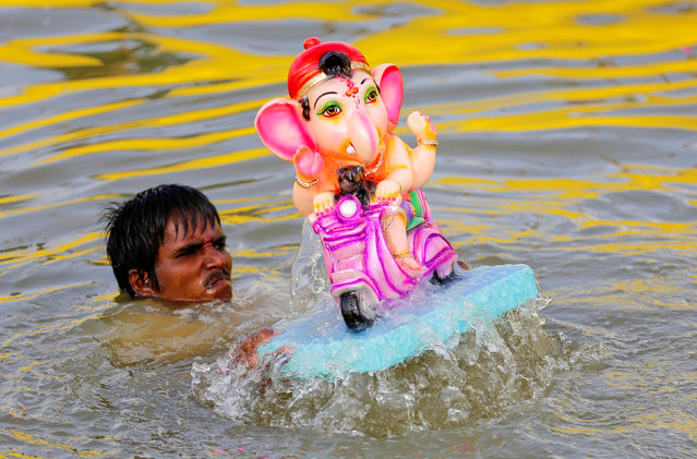 A man immerses an idol of Hindu god Ganesh, the deity of prosperity, in a pond on the second day of Ganesh Chaturthi festival in Ahmedabad, India, September 6, 2016. (Photo by Amit Dave/Reuters)