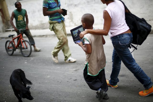 A boy holds a portable video player as he walks with his mother in Havana September 18, 2015. (Photo by Edgard Garrido/Reuters)