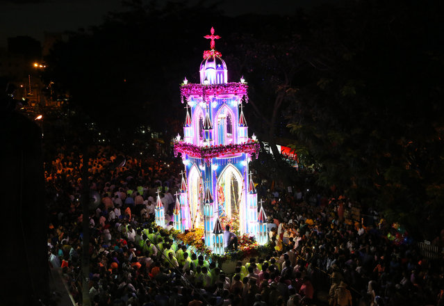 Worshippers crowd around a chariot carrying a statue of Virgin Mary outside St. Mary's Basilica, the oldest church in Bangalore, on the occasion of the Feast of Nativity of the Virgin Mary, in Bangalore, India, Thursday, September 8, 2016. (Photo by Aijaz Rahi/AP Photo)