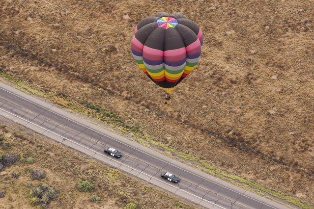 A hot air balloon floats over a road during the 2015 Albuquerque International Balloon Fiesta in Albuquerque, New Mexico, October 5, 2015. (Photo by Lucas Jackson/Reuters)