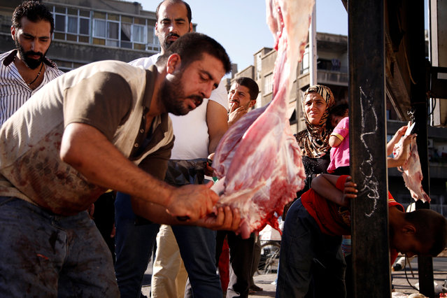 People watch a butcher cut meat during the first day of Eid al-Adha celebrations in Damascus, Syria September 12, 2016. (Photo by Omar Sanadiki/Reuters)