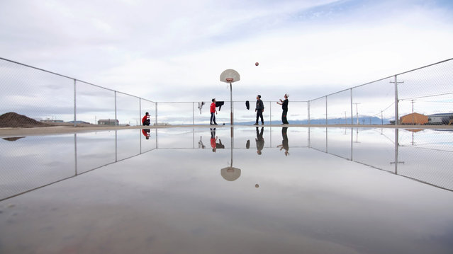 """The Arctic League"". The brand new basketball court in Pond Inlet, Nunavut sees action just after a rain. The playing season is short with only three months of the year in the pluses. But, with 24-hour daylight, games go long and late. Photo location: Pond Inlet, Nunavut, Canada. (Photo and caption by Chris Paetkau/National Geographic Photo Contest)"