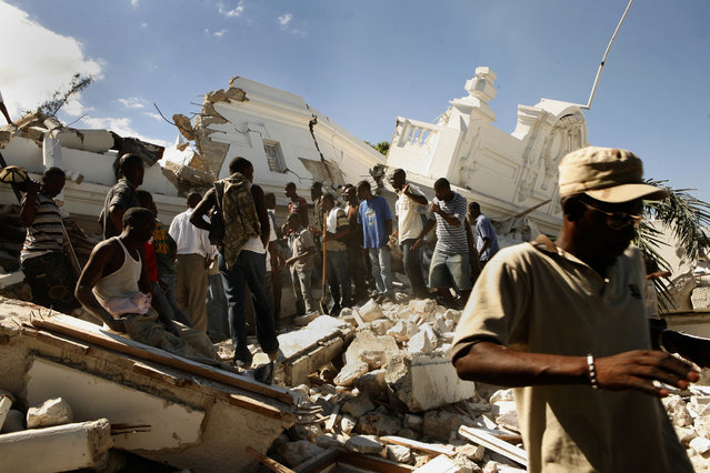 The Department of Justice was flattened by the earthquake. Men gather to try to get to those still buried in the rubble without any assistance in Port-au-Prince, Haiti, January 13, 2010. (Photo by Carolyn Cole/Los Angeles Times via Getty Images)