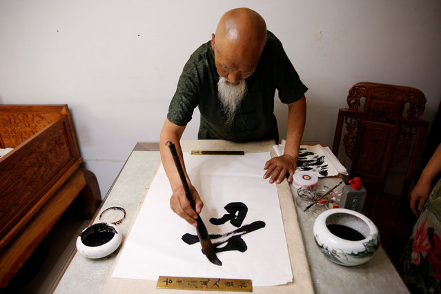 Kung Fu master Li Liangui practices calligraphy at his apartment in Beijing, China, July 2, 2016. (Photo by Kim Kyung-Hoon/Reuters)