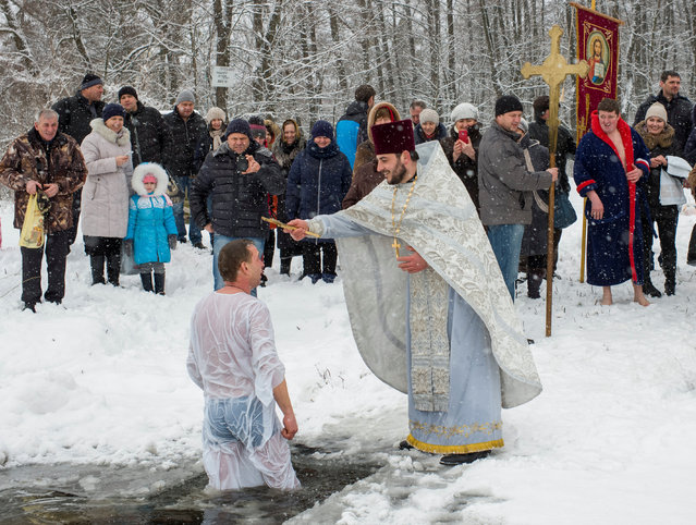 A priest takes part in a religious ceremony as a man takes a dip in icy water during Orthodox Epiphany celebrations in the village of Ivankovychi, Ukraine on January 19, 2018. (Photo by Gleb Garanich/Reuters)