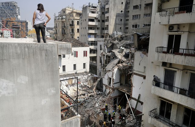 A woman looks on from a rooftop as rescue workers dig through the rubble of a badly damaged building in Lebanon's capital Beirut, in search of possible survivors from a mega-blast at the adjacent port one month ago, after scanners detected a pulse, on September 4, 2020. Lebanese rescuers scoured rubble for a possible survivor in Beirut after the detection of a pulse drew crowds hopeful of a miracle one month on from a devastating explosion. (Photo by Joseph Eid/AFP Photo)
