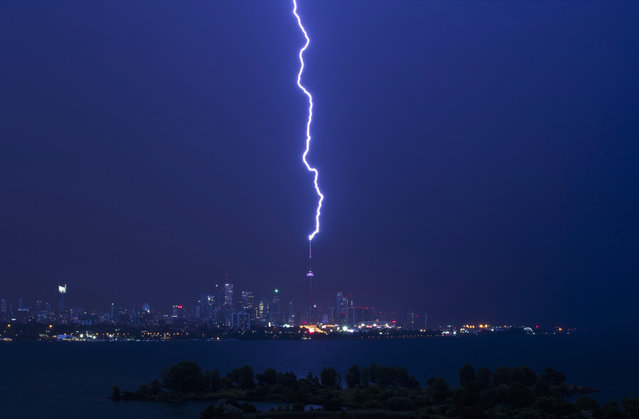 A lightning bolt strikes the CN Tower during an electrical storm in Toronto, Thursday, July 14, 2016. Heavy winds and rain brought down trees and power lines overnight in Toronto. (Photo by Mark Blinch/The Canadian Press via AP Photo)