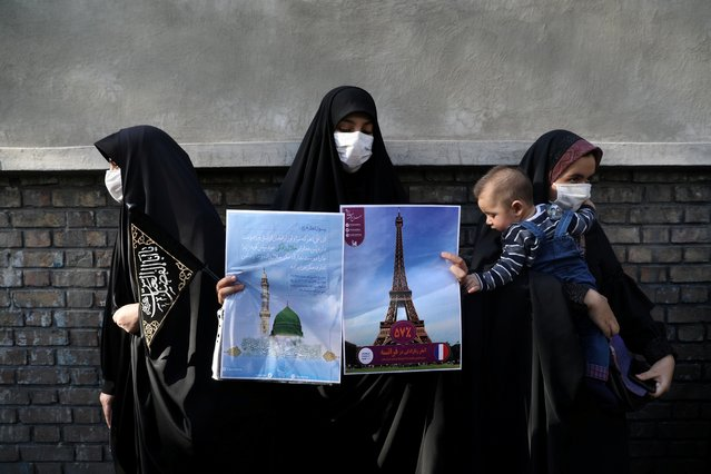 A protester holding banner of France's Eiffel Tower and Al Masjid Nabawi of Saudi Arabia, takes part in a protest to condemn the French magazine Charlie Hebdo for republishing cartoons insulting the Holy Prophet of Islam, in front of the French Embassy in Tehran, Iran on September 9, 2020. (Photo by Majid Asgaripour/WANA via Reuters)