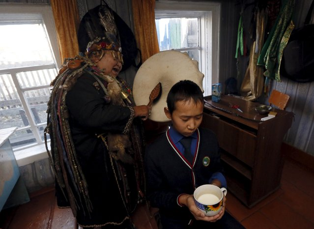 Anisya Mongush (L), a female shaman representing the so-called Dungur society, conducts a session to clarify and improve the relations of a customer, a local boy, with other people at her residence in the town of Kyzyl, the administrative centre of Tuva region, Southern Siberia, Russia, October 7, 2015. (Photo by Ilya Naymushin/Reuters)