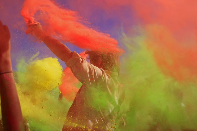 People throw paint powder in the air during the holi one colour Festival held in the city of Cape Town, South Africa, Saturday, March 2, 2013.  Thousands of people are taking part in the festival by throwing coloured paint powder at each other to express freedom and the colour of everyday life. (Photo by Schalk van Zuydam/AP Photo)