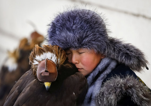 A young hunter rests next to his tamed golden eagle during an annual hunters competition at Almaty hippodrome, Kazakhstan February 9, 2018. (Photo by Shamil Zhumatov/Reuters)