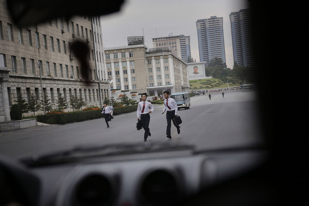 North Korean students run as they make their way to school during morning rush hour as seen through the wind screen of a car on Wednesday, September 28, 2016, in Pyongyang, North Korea. (Photo by Wong Maye-E/AP Photo)
