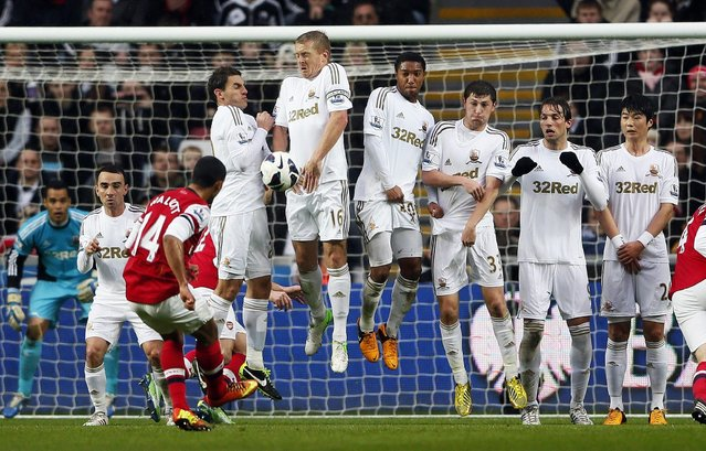 Arsenal's Theo Walcott (L) takes a free kick against Swansea City during their English Premier League soccer match at the Liberty Stadium in Swansea, March 16, 2013. (Photo by Stefan Wermuth/Reuters)