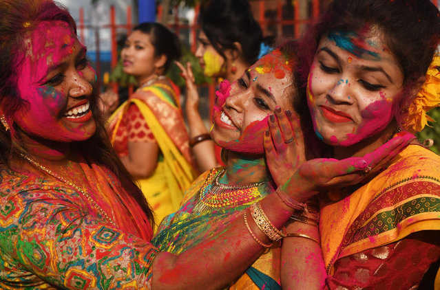 Indian students smear coloured powder during an event to celebrate the Hindu festival of Holi in Kolkata on February 26, 2018. Holi, the popular Hindu spring festival of colours is observed in India at the end of the winter season on the last full moon of the lunar month, and will be celebrated on March 1 this year. (Photo by Dibyangshu Sarkar/AFP Photo)