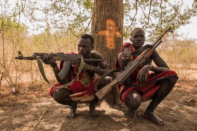 Sudanese cattle keepers from Dinka tribe Makal Maker (R) and Achiek Butich pose with the guns for their protection at their cattle camp in Mingkaman, Lakes State, South Sudan, on March 2, 2018. (Photo by  Stefanie Glinski/AFP Photo)