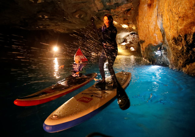 A mother and her daughter paddle during a Stand Up Paddle (SUP) race of the Alpine Lakes Tour, on Europe's biggest underground lake, in St-Leonard, Switzerland, March 10, 2018. (Photo by Denis Balibouse/Reuters)