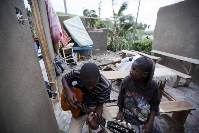 A man sits inside of what is left of his home with his cousin after it was damaged by Hurricane Matthew in Saint-Louis, Haiti, Wednesday, October 5, 2016. (Photo by Dieu Nalio Chery/AP Photo)
