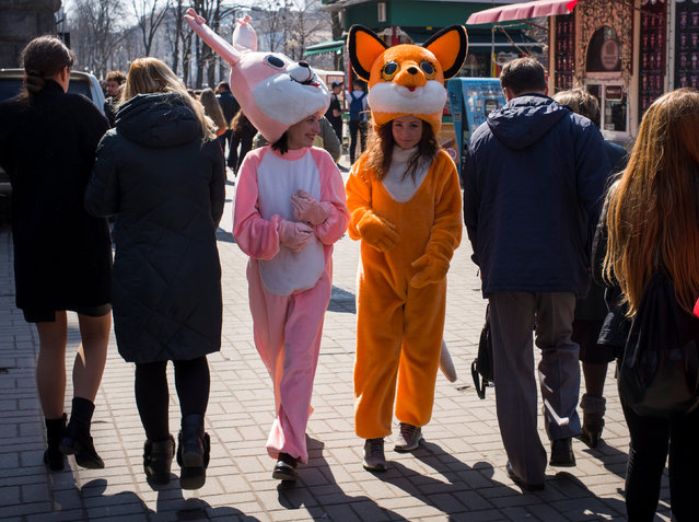 Women dressed as a rabbit and a fox, who pose for pictures with tourists, walk in central Kiev, Ukraine April 4, 2018. (Photo by Gleb Garanich/Reuters)