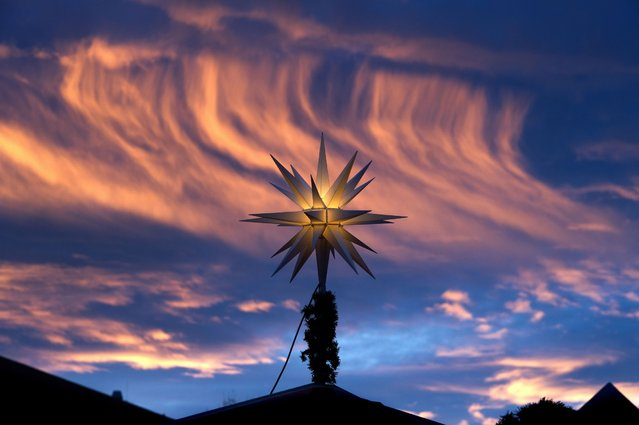 A Christmas star on top of a sales booth is pictured against the colorful morning sky at the Christmas market in Dresden, eastern Germany, Friday, December 12, 2014. (Photo by Arno Burgi/AP Photo/DPA)