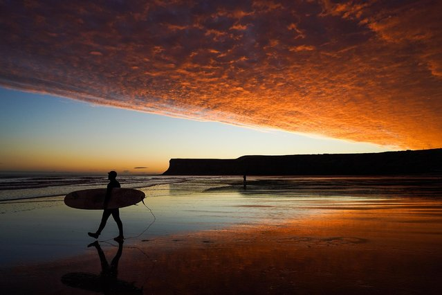 A surfer walks to the water as clouds are lit by a dramatic sunrise over Saltburn beach on October 27, 2020 in Saltburn By The Sea, England. (Photo by Ian Forsyth/Getty Images)