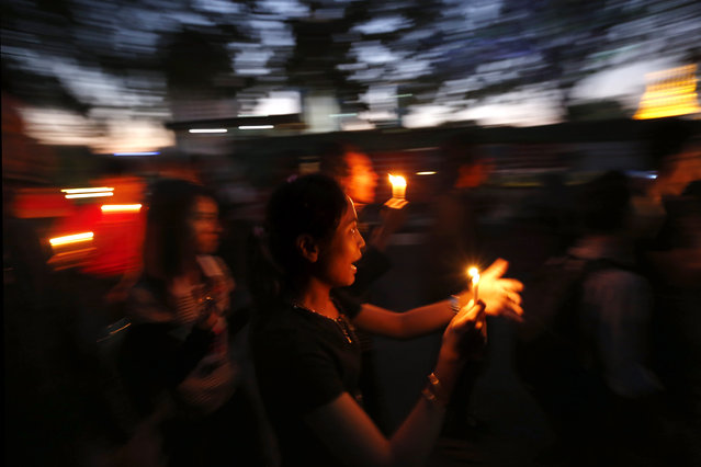 Student activists hold candles as they march during a prayer for casualties of Chinese-backed copper mine crackdown, in Yangon, Myanmar, December 23, 2014. (Photo by Lynn Bo Bo/EPA)