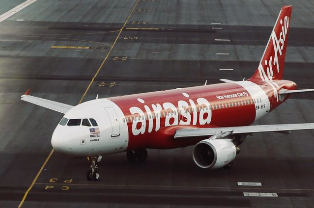 An AirAsia plane is seen on the runway at Kuala Lumpur International Airport in this August 19, 2014 file photo. An AirAsia flight carrying 155 people from the Indonesian city of Surabaya to Singapore lost contact with air traffic control on December 28, 2014, officials in the region and the budget carrier said. Flight QZ 8501, an Airbus 320-200, lost contact with the Jakarta air traffic control tower at 6:17 a.m. (Photo by Olivia Harris/Reuters)