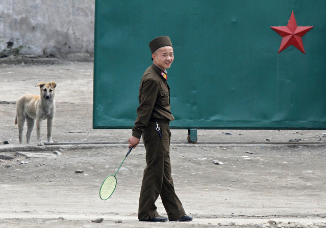 A North Korean soldier holds a badminton racket on the banks of Yalu River near the North Korean town of Sinuiju, opposite the Chinese border city of Dandong, May 20, 2011. (Photo by Jacky Chen/Reuters)