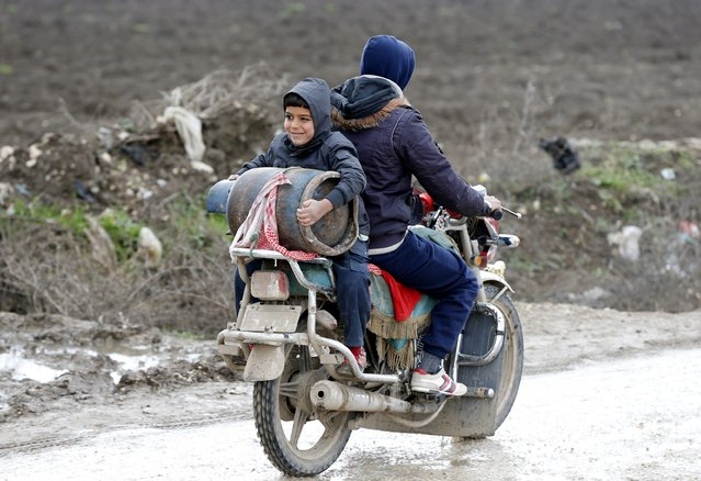 A Syrian refugee boy carries a gas canister on a motorcycle near a makeshift settlement in Bar Elias in the Bekaa valley January 5, 2015. (Photo by Mohamed Azakir/Reuters)