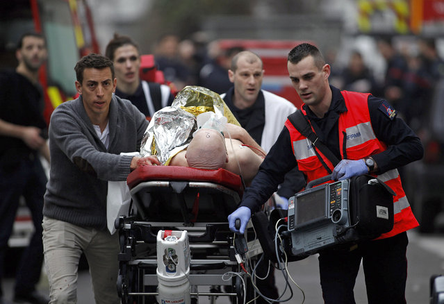 An injured person is evacuated outside the French satirical newspaper Charlie Hebdo's office, in Paris, Wednesday, January 7, 2015. Police official says 11 dead in shooting at the French satirical newspaper. (Photo by Thibault Camus/AP Photo)