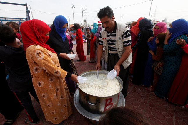 Women who recently fled the Islamic State's stronghold on the outskirts of Mosul queue to receive food at the school at Debaga camp, on the outskirts of Erbil, Iraq October 28, 2016. (Photo by Alaa Al-Marjani/Reuters)